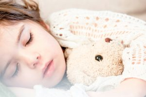 Kids with sleep apnea holding a teddy bear.